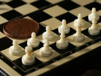 7548-close-up-of-a-miniature-chess-set-with-a-coin-pv-326x245-3464209