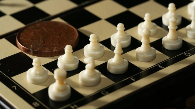 7548-close-up-of-a-miniature-chess-set-with-a-coin-pv-678x381-7879911